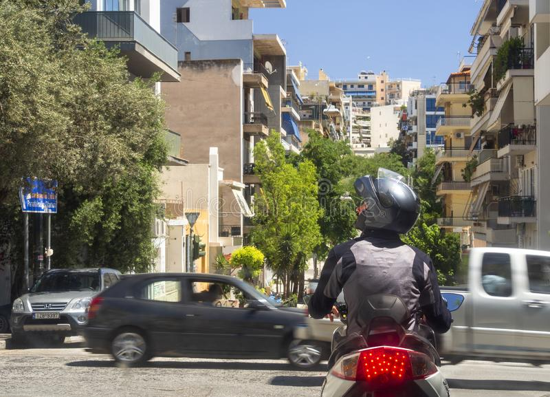 Athens, Greece. August 2019: a Motorcyclist in gear and helmet stopped at a traffic light on a street in the center of the Greek c royalty free stock image
