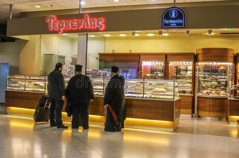 1-8-2018 Athens Greece - Greek orthodox priests chat with a traveler at a bakery at the airport.  royalty free stock image