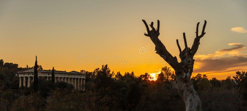 Athens Greece. Hephaestus temple at sunrise time, sun rising against orange color sky. View from Monastiraki area, banner royalty free stock photo