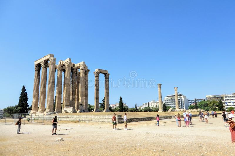 A group of tourists walking around admiring the remains of Temple of Olympian Zeus in Athens, Greece on a beautiful hot summer day royalty free stock image