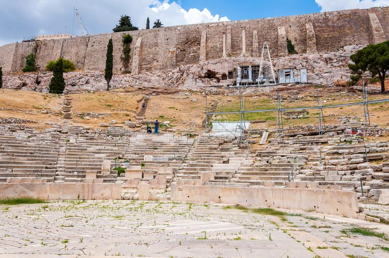 Ancient ruins of amphitheater under the main holy hill of Acropolis in Athens, Greece stock photo
