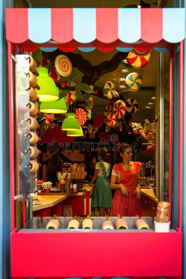 Colorful fairy tales theme shopfront decoration of sweet candies shop with beautiful young lady sellers in pink and blue dress royalty free stock photos