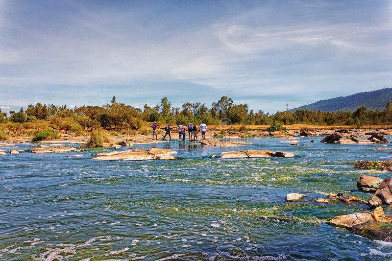 Athi River in Kenya. People form a line to cross the waters of the Athi River in Thika, Kenya. The Athi River is Kenya`s second longest river stock photo