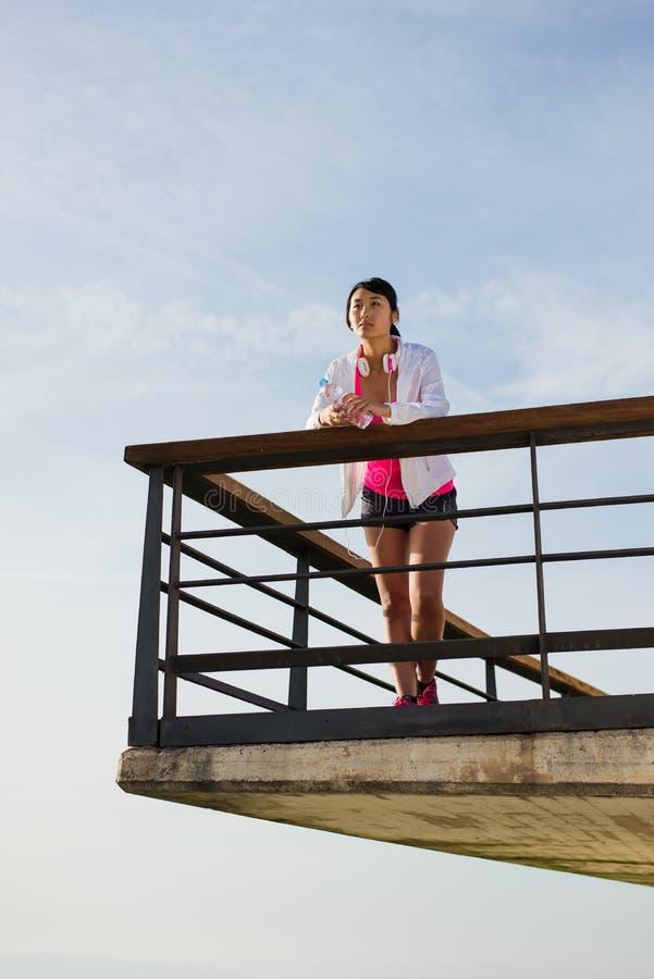 Athlète asiatique féminin se reposant après séance d'entraînement urbaine images stock