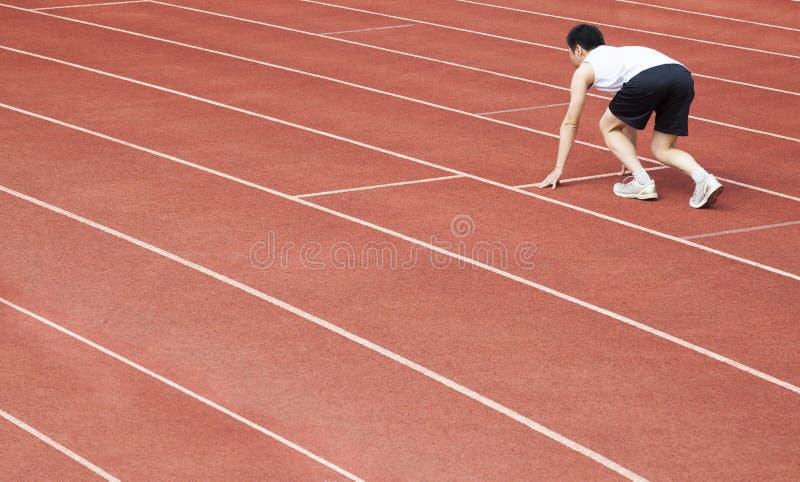 athlète au début de la ligne au stade images stock