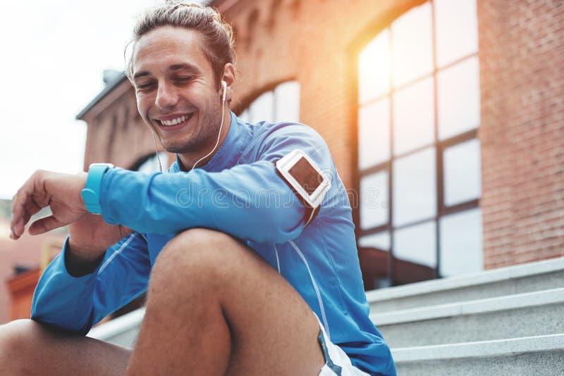 Athlète bel vérifiant le temps sur les montres intelligentes après bonne session de séance d'entraînement sur la rue, se reposant photos stock