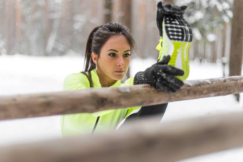Athlète convenable de femme faisant la jambe de tendon étirant des exercices dehors en bois Parc extérieur de exercice modèle d'h photo libre de droits
