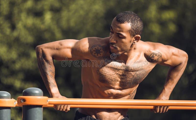 Athlète d'afro-américain faisant des exercices sur des barres parallèles photo stock