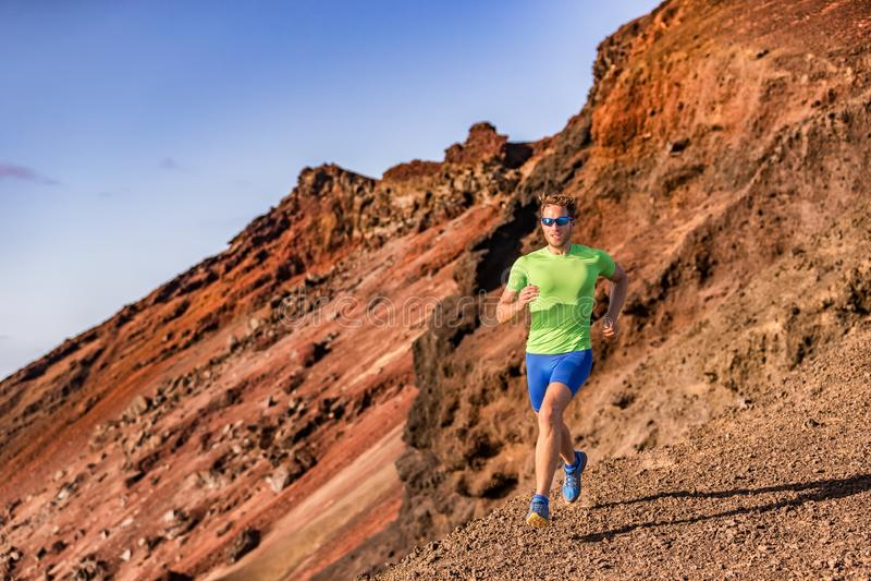 Athlète d'homme de coureur de traînée courant ultra dans le chemin rocheux de montagne en nature Paysage backcountry de montagnes image stock