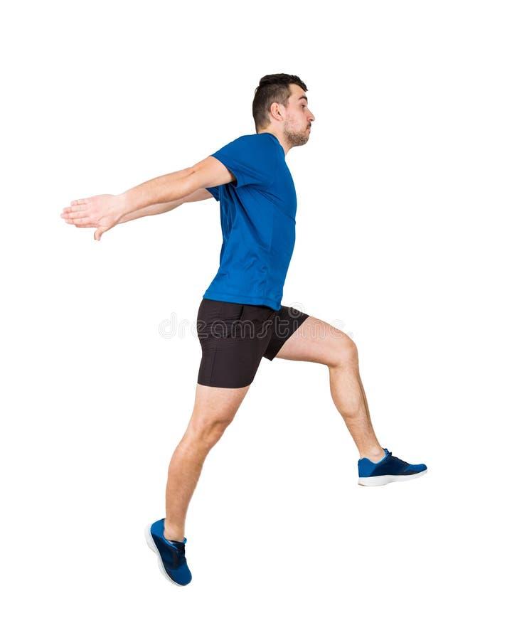 Athlète d'homme sautant par-dessus l'obstacle imaginaire d'isolement sur le fond blanc Le jeune coureur de type utilisant les vêt photos libres de droits
