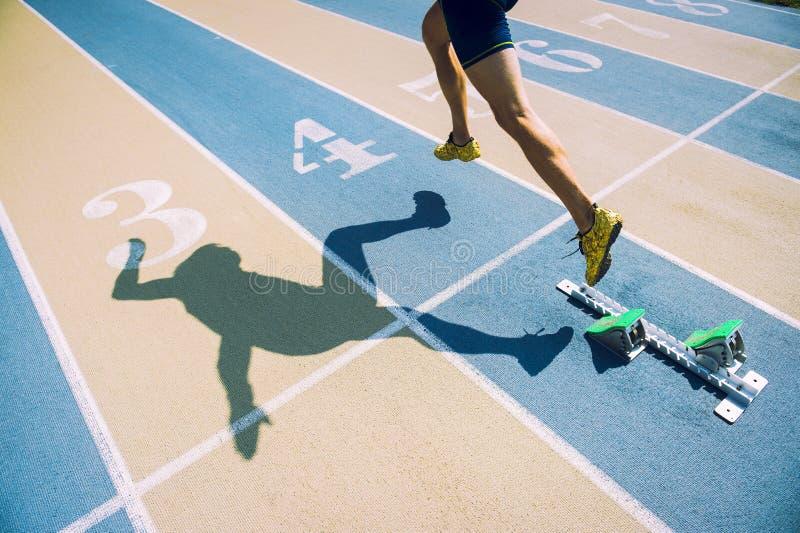 Athlète dans des chaussures d'or sprintant à travers la ligne de départ photographie stock libre de droits