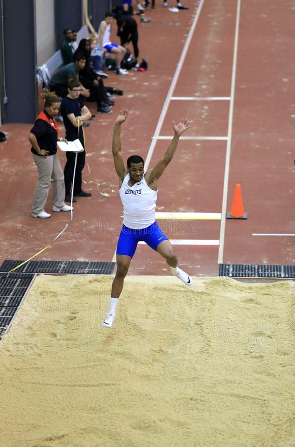 Athlète dans le midflight de son long saut photographie stock