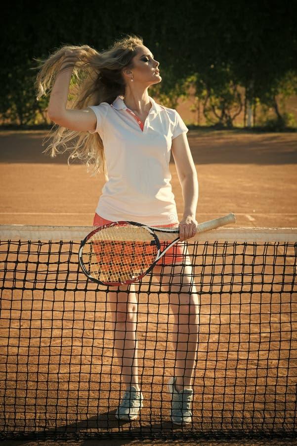 Athlète de femme dans la raquette de tennis uniforme sexy de prise au filet images stock