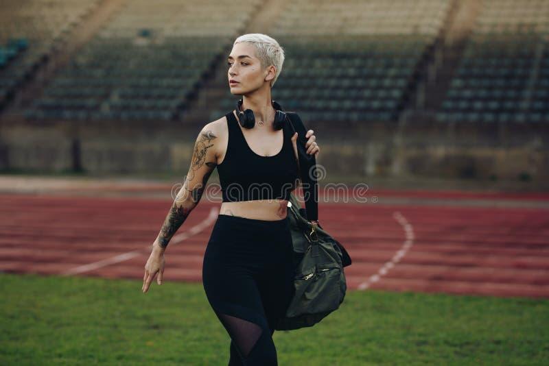 Athlète de femme marchant à l'intérieur d'un stade d'athlétisme photo stock