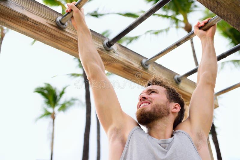 Athlète de forme physique d'exercice s'exerçant sur des barres de singe images libres de droits