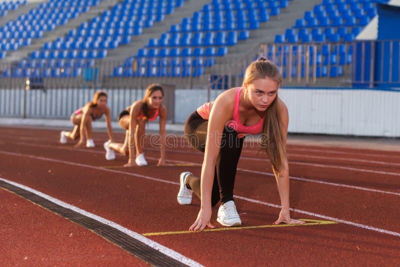 Athlète de jeune femme à la position de départ prête à commencer une course images stock