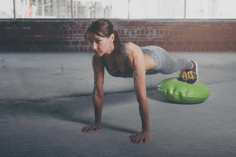 Athlète de jeune femme dans des pousées de vêtements de sport sur la boule gymnastique image libre de droits
