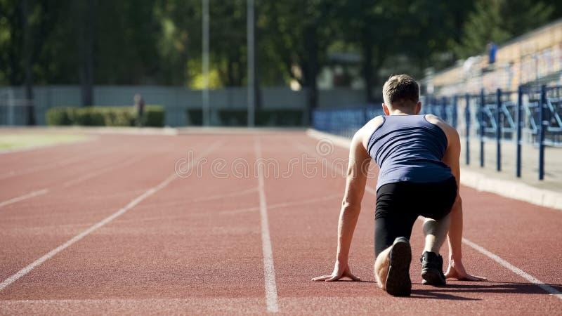 Athlète en position de départ à courir sur le stade, formation professionnelle de sportif photos stock
