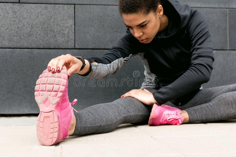 Athlète féminin étirant des jambes photos libres de droits