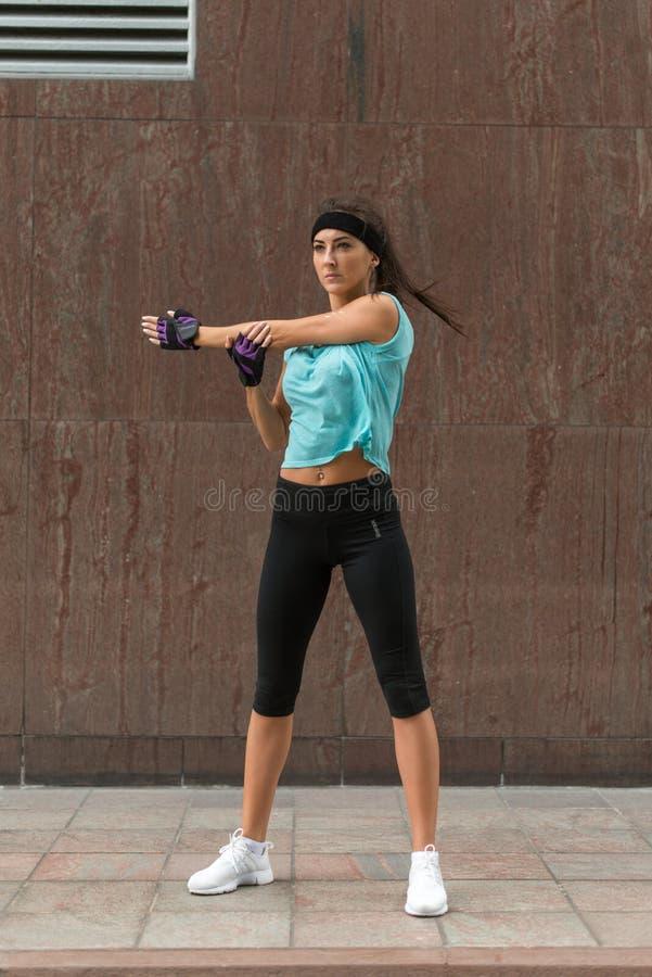 Athlète féminin étirant son bras La jeune femme faisant l'échauffement s'exerce avant le fonctionnement sur le trottoir de la rue photographie stock