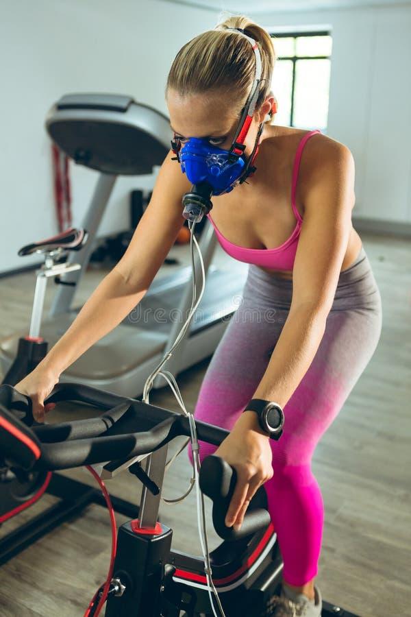 Athlète féminin avec le masque à oxygène s'exerçant avec le vélo d'exercice dans le studio de forme physique photos stock