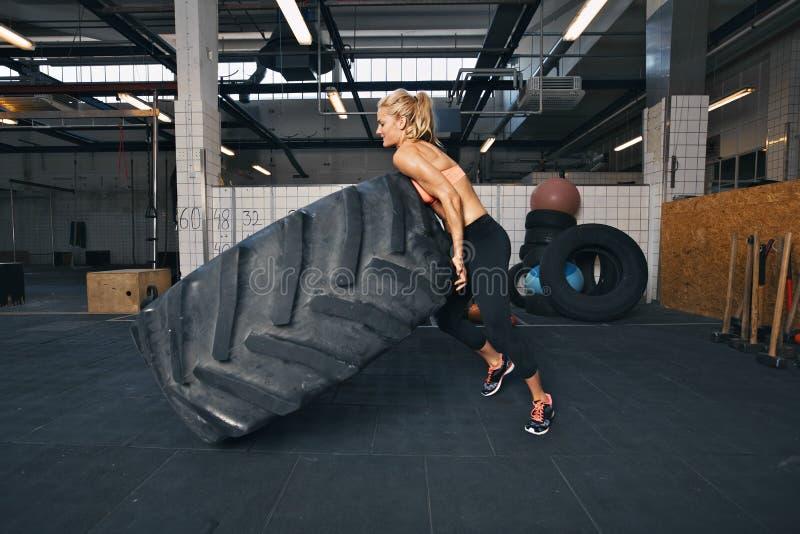 Athlète féminin convenable renversant un pneu énorme image stock