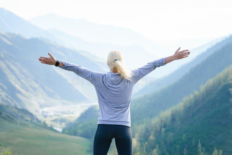 Athlète féminin dans l'habillement de sports sur la montagne photos stock