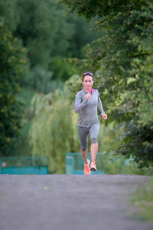 Athlète féminin de coureur courant sur la traînée de parc Joggi de forme physique de femme photos libres de droits