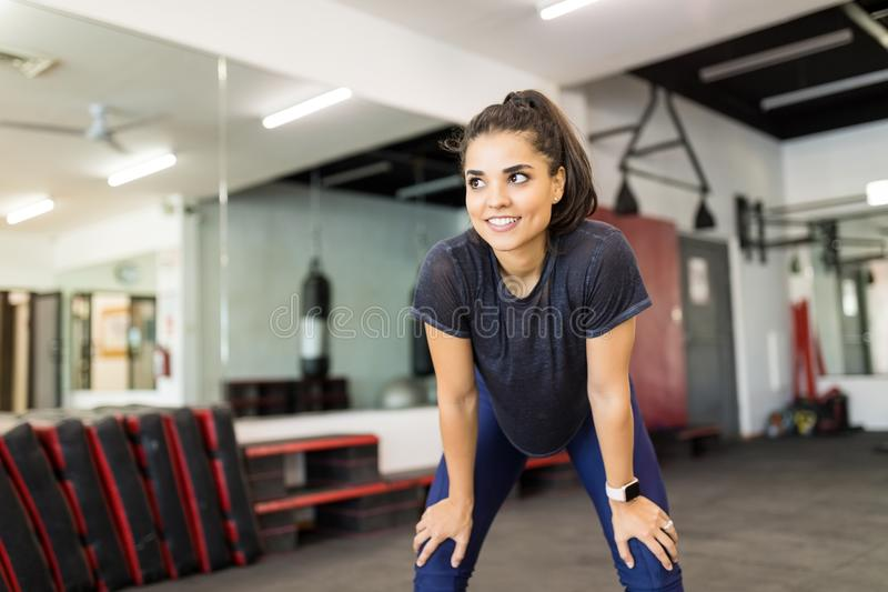 Athlète féminin de sourire Relaxing After Exercise dans le gymnase image stock