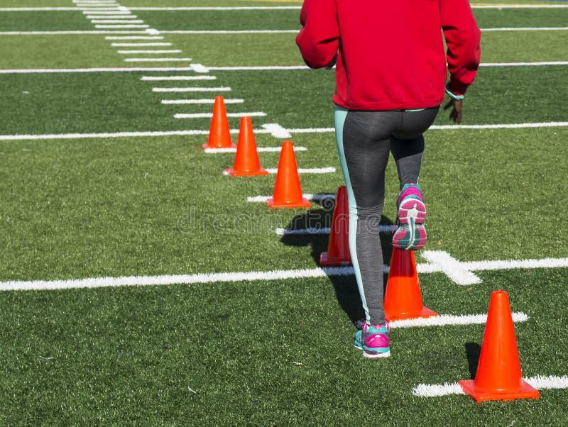 Athlète féminin effectuant les exercices fonctionnants au-dessus des cônes photos stock