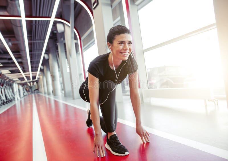 Athlète féminin en position prêt à fonctionner femme prête pour le sprint photographie stock