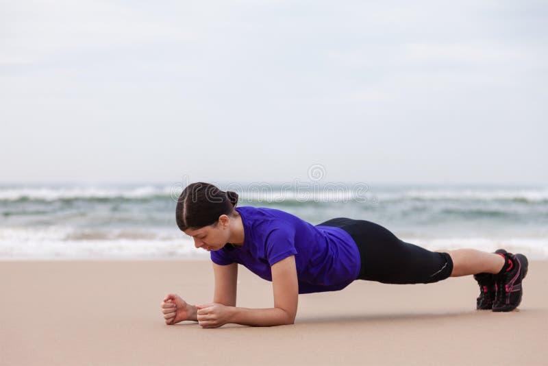 Athlète féminin exécutant l'exercice de planche image libre de droits