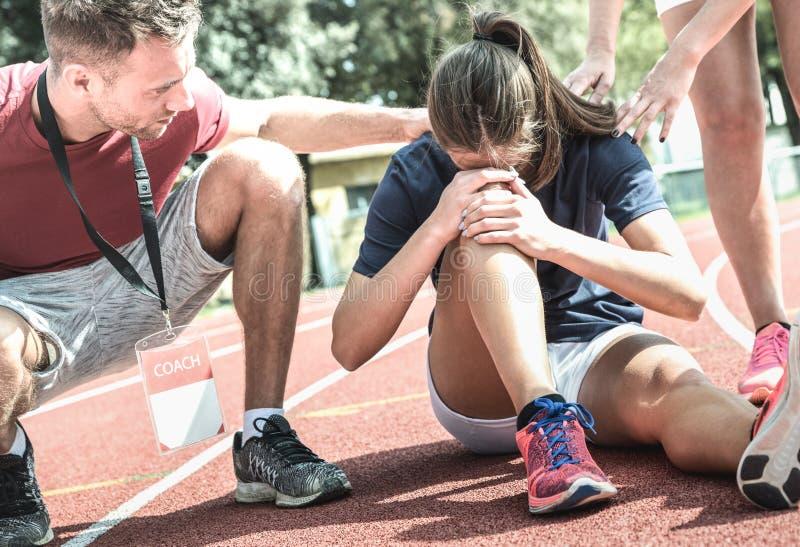 Athlète féminin obtenant blessé pendant la formation courue sportive - entraîneur masculin prenant le soin sur l'élève de sport a photos libres de droits