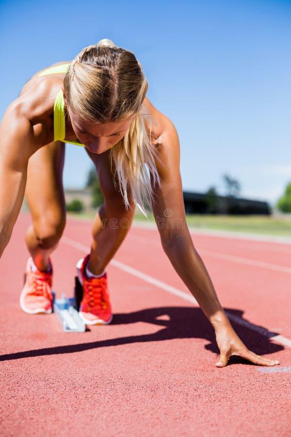 Athlète féminin prêt à fonctionner sur la voie courante photo stock