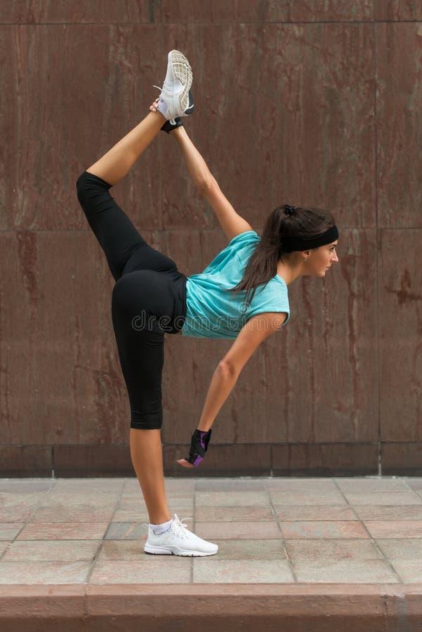 Athlète féminin réchauffant en étirant ses jambes dehors Jeune femme sportive faisant l'exercice fendu de position de yoga sur photographie stock