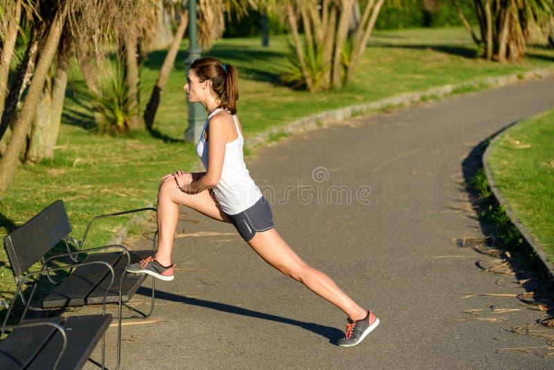 Athlète féminin réchauffant et s'étirant pour le fonctionnement photographie stock