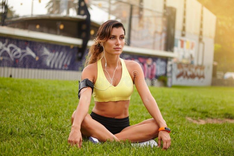 Athlète féminin songeur se reposant et regardant loin images libres de droits