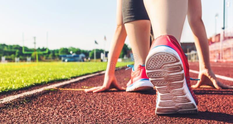 Athlète féminin sur la ligne de départ d'une voie de stade images stock