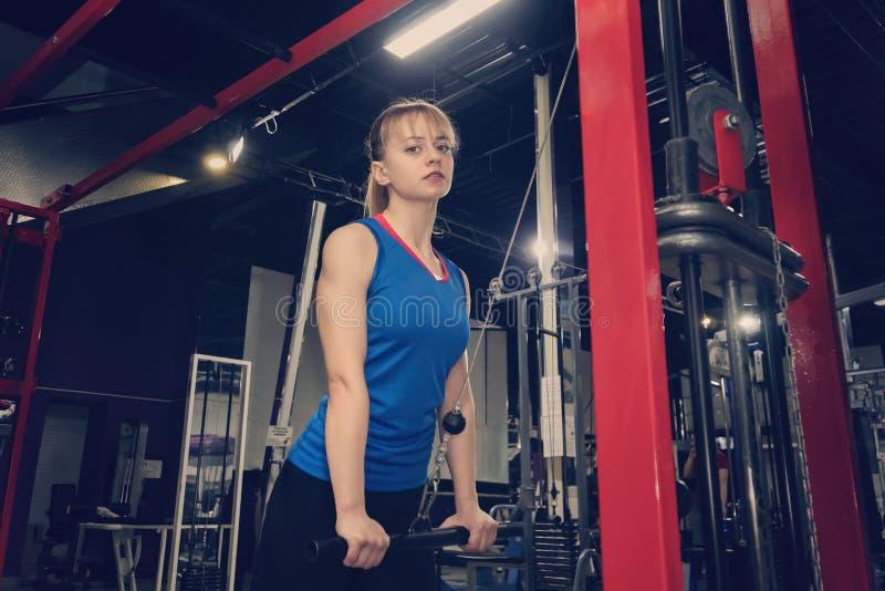 Athlète féminin sur la machine à ramer sur la concurrence croisée soulève la barre Soulevez les poids L'athlète dans un costume b images libres de droits