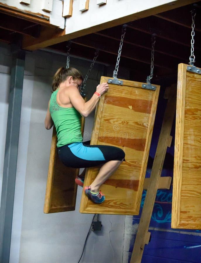 Athlète féminin transférant à partir d'un mur de flottement au prochain images stock