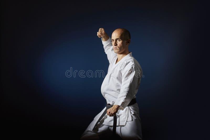 Athlète faisant des exercices formels de karaté sur le fond bleu avec le gradient image libre de droits