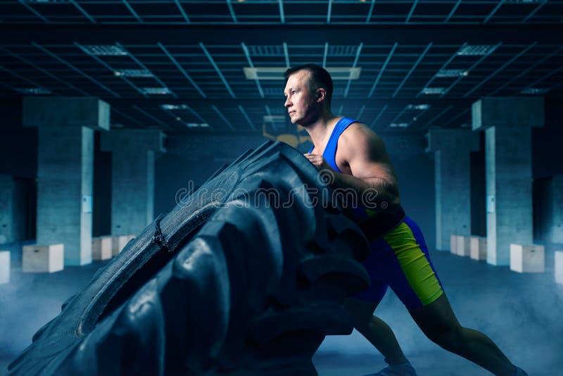 Athlète faisant l'exercice avec le pneu de camion, crossfit photos stock