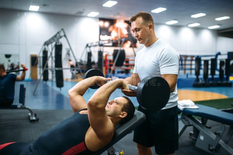 Athlète faisant l'exercice sous le contrôle d'instructeur photo libre de droits