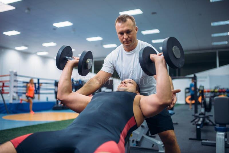 Athlète faisant l'exercice sous le contrôle d'instructeur photographie stock