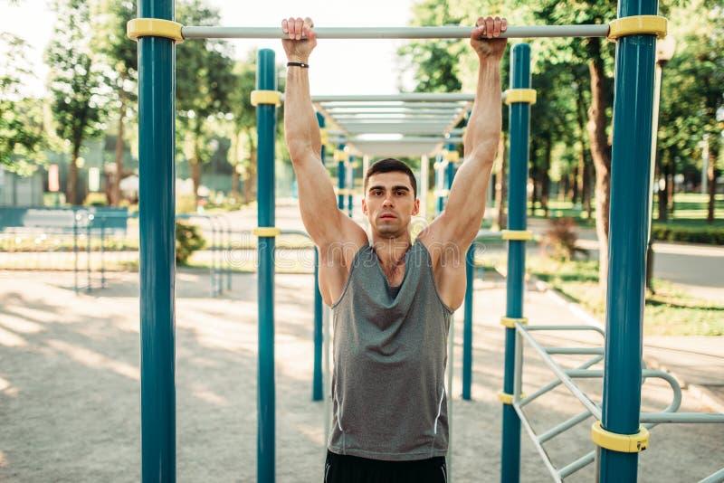 Athlète faisant l'exercice sur la barre horizontale extérieure photographie stock