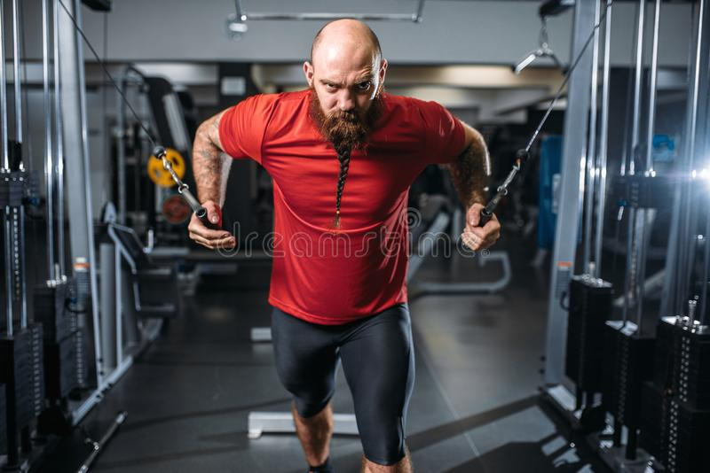 Athlète fort, s'exerçant sur la machine d'exercice image stock