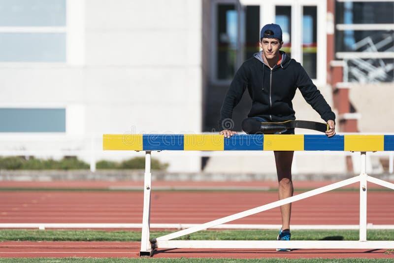 Athlète handicapé d'homme s'étirant avec la prothèse de jambe Paralympic image stock
