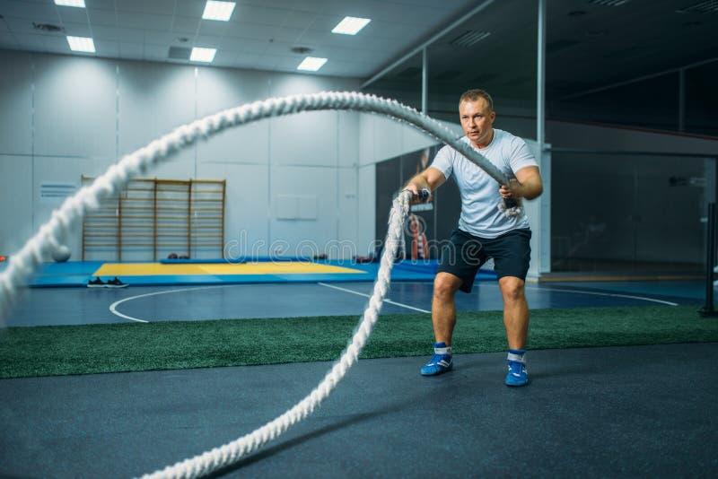 Athlète masculin avec des cordes dans le gymnase, séance d'entraînement de crossfit images stock