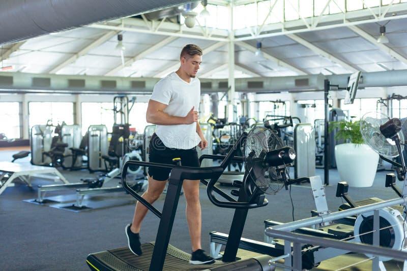 Athlète masculin courant sur le tapis roulant dans le studio de forme physique photographie stock libre de droits
