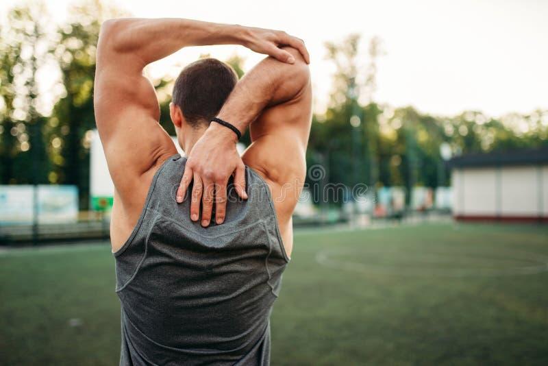 Athlète masculin faisant étirant l'exercice, vue arrière photographie stock libre de droits